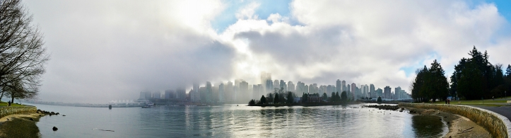 Panoramic view of Downtown Vancouver from Stanley Park.With a slight break of clouds and fog this panoramic view of Downtown Vancouver reveals its beautiful skyline as seen from Stanley Park.
